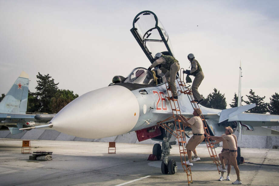 FILE - In this Oct. 22, 2015 file photo, Russian air force pilots, assisted by ground crew, climb into their fighter jet at Hemeimeem airbase, Syria. Russia's defense ministry said Tuesday, March 15, 2016, that the first group of warplanes stationed at the Russian air base in Syria has left for home following a pullout order from President Vladimir Putin.(AP Photo/Vladimir Isachenkov, File)