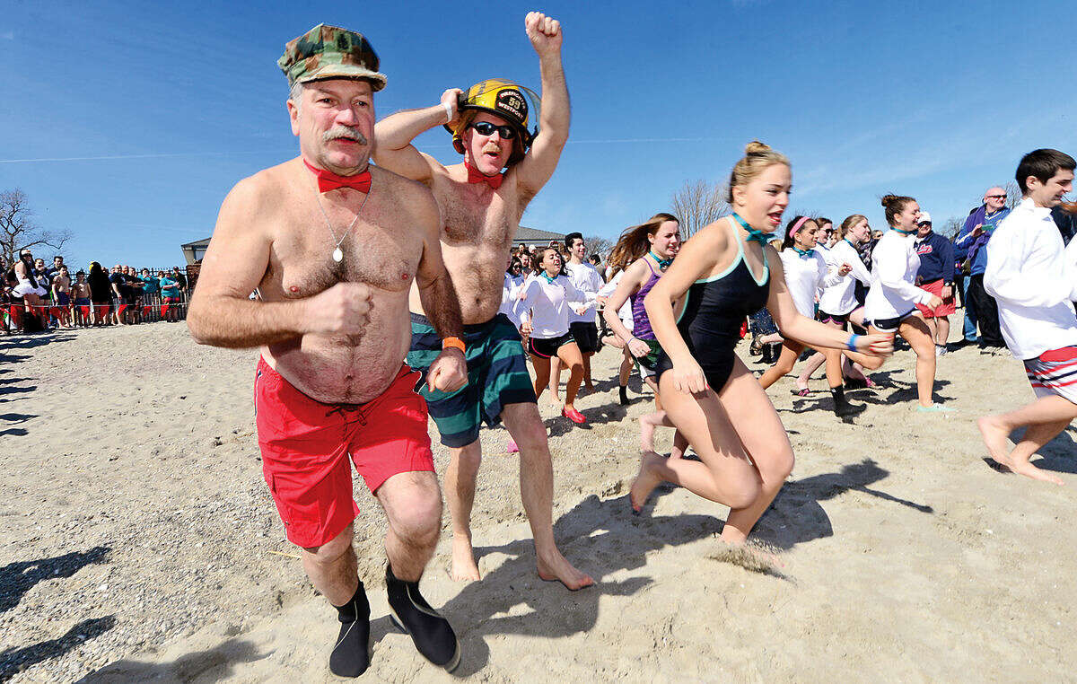 Hour photo / Erik Trautmann Westport firefighters head into the water during the 2016 Westport Penguin Plunge at Compo Beach Saturday to benefit The Special Olympics.