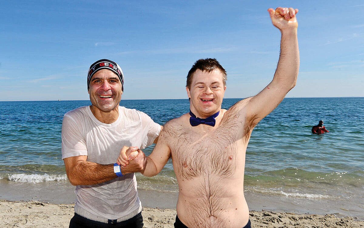 Hour photo / Erik Trautmann Pat Lopiano and Peter Brandeen exit the water during the 2016 Westport Penguin Plunge at Compo Beach Saturday to benefit The Special Olympics.