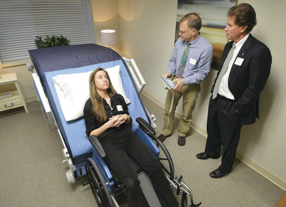 Hour photo / Alex von KleydorffNext Health Chief Engineer David Beckstrom demonstrates the Zero-Lift Patient Transfer System to state Senator Scott Frantz, with the help of Post Implementation Manager Ariana Olson on the system.