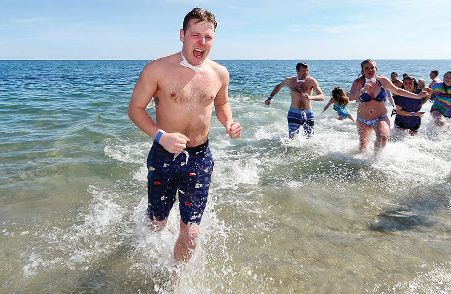 Hour photo / Erik Trautmann Jake DeLuca exits the water during the 2016 Westport Penguin Plunge at Compo Beach Saturday to benefit The Special Olympics.