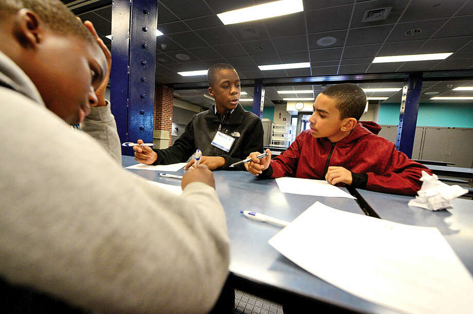 Hour photo / Erik Trautmann Children from the Norwalk Housing Authority after school programs including Sean Paul Joseph, Joshua Davis and George Dacruz work on their resumes while attending the Careers on Fleek event at the Maritime Aquarium Friday evening. The event provided middle school students with help with their career paths by playing games focusing on public speaking, personal finance, resume building and career opportunities and how to successfully join the work force.
