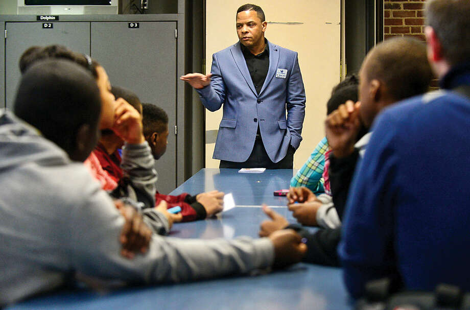 Hour photo / Erik Trautmann Maritime Aquarium president Dr. Brian Davis greets children from the Norwalk Housing Authority after school programs who attended the Careers on Fleek event at the Maritime Aquarium Friday evening. The event provided middle school students with help with their career paths by playing games focusing on public speaking, personal finance, resume building and career opportunities and how to successfully join the work force.