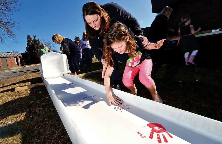 Miller-Driscoll School first-grader Sophia Solomon signs and puts her hand print on a steel beam with the help of volunteer Sarah Prevett during a ceremony celebrating the $50 million renovation project Wednesday at the school.