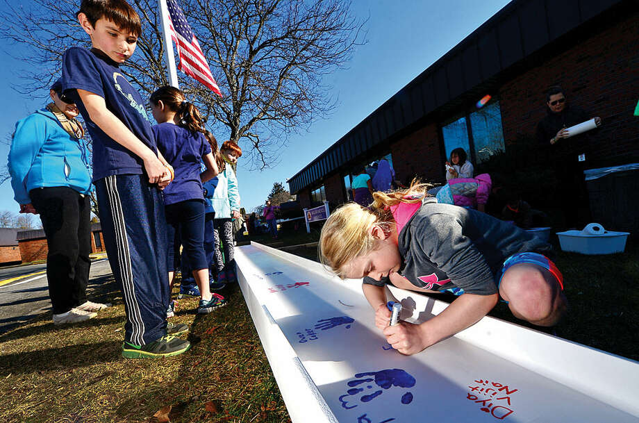 Hour photo / Erik Trautmann Miller-Driscoll School students including second grader Emma Van Heyst sign and put their handprints on steel beams to be incorporated in the new construction of the $50-million renovation project Wednesday at the school.