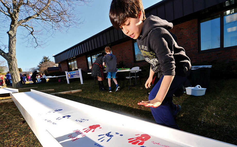 Hour photo / Erik Trautmann Miller-Driscoll School students including second grader Avi Wilson-Spiro sign and put their handprints on steel beams that will be incorporated in the new construction of the $50-million renovation project at the school Wednesday .
