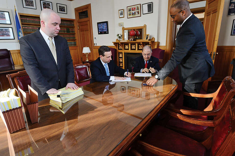 Hour photo / Erik Trautmann New Senate Majority Leader Bob Duff (D-25), second from left, signs bills with fellow senator Martin Looney before the joint legislative session and gubenatorial budget address Wednesday at the state capitol in Hartford.