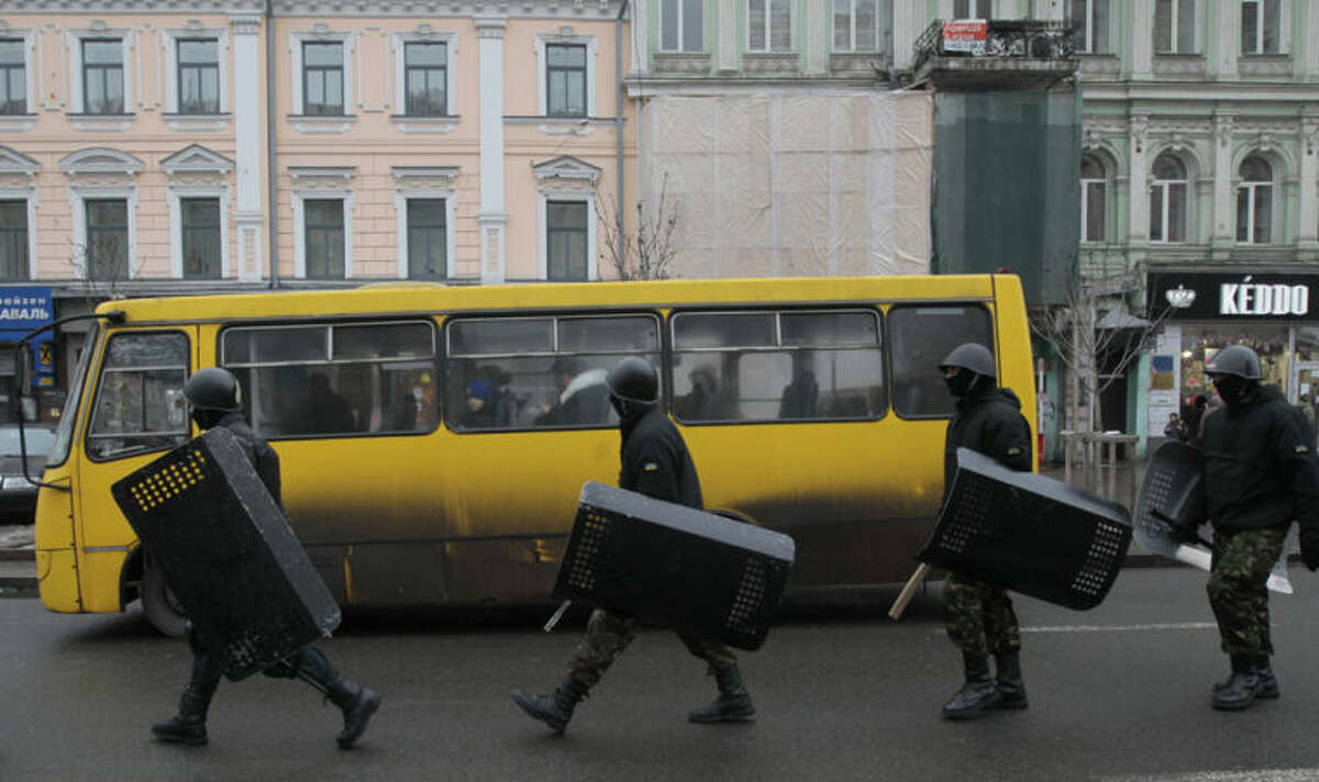 Members of Ukrainian protesters' self-defense corps move down a Khreschatyk street during a confrontation with demonstrators opposed to the protests in Kiev, Ukraine, Saturday, Feb. 8, 2014. Thousands of people angered by months of anti-government protests in the Ukrainian capital converged on one of the protesters' barricades Saturday, but retreated after meeting sizeable resistance. (AP Photo/Sergei Chuzavkov)