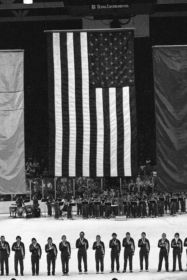 FILE --In this Feb. 24, 1980 file photo, members of the 1980 USA Olympic ice hockey team stand on the ice during the playing of the National Anthem at the awards ceremonies. The American team won the gold medal. It's been more than three decades since his landmark goal became the centerpiece of the U.S. Olympic hockey team's Miracle on Ice. For 60-year-old Mike Eruzione, it still seems like only yesterday. (AP Photo, File)