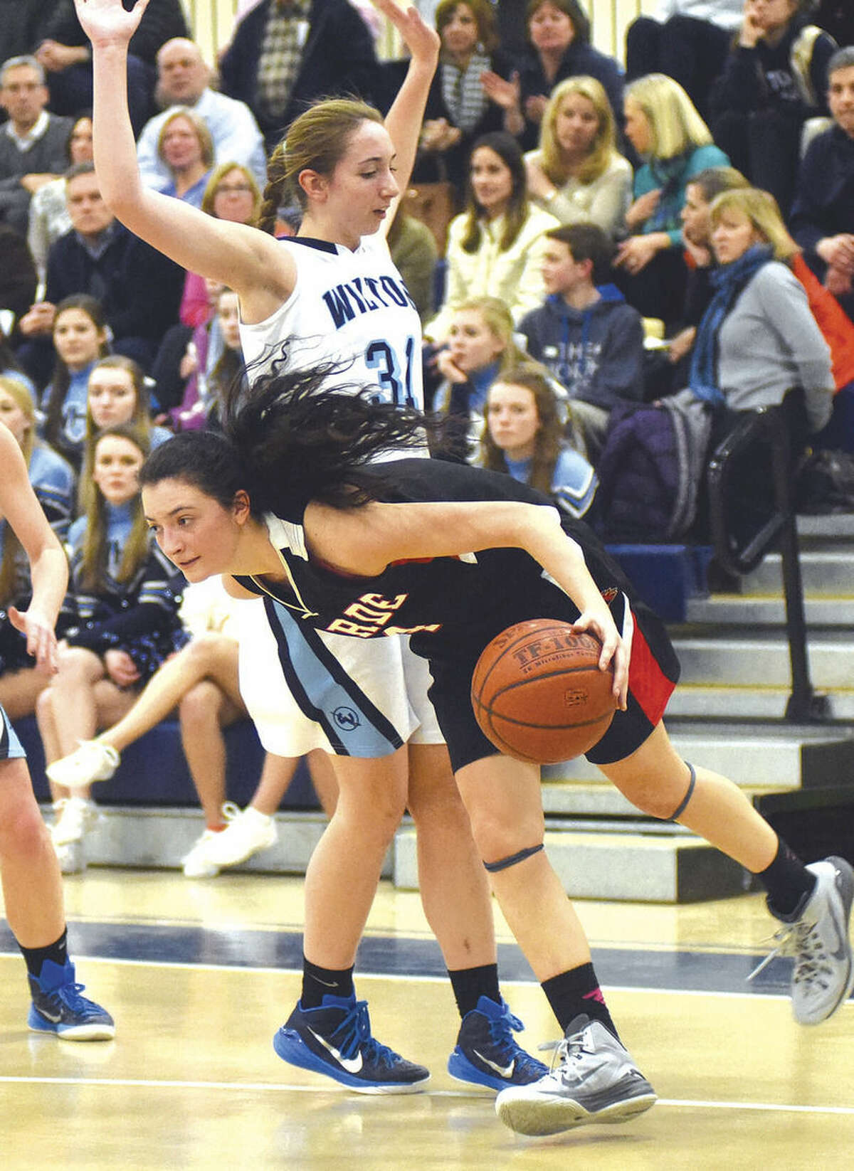 Hour photo/John Nash Wilton's Christina Holmgren, top, defends atop the press as Fairfield Warde guard Lejla Markovic reverses direction during Wednesday's FCIAC regular season finale at the Zeoli Field House in Wilton.