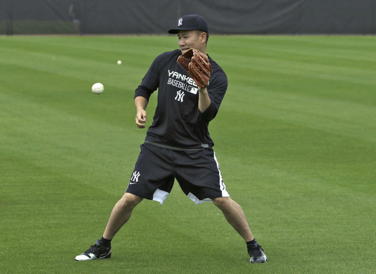 New York Yankees pitcher Masahiro Tanaka, of Japan, fields the baseball while working out at the Yankees' minor league complex Tuesday, Feb. 17, 2015, in Tampa, Fla. (AP Photo/Chris O'Meara)