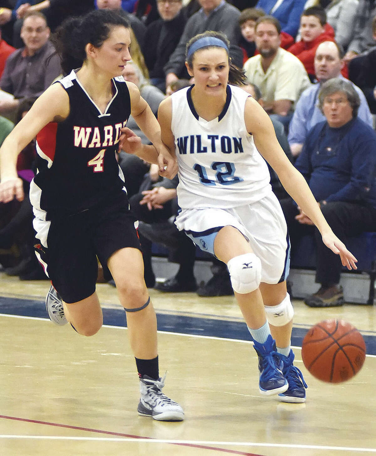 Hour photo/John Nash Haley English of Wilton, right, pushes the ball past Fairfield Warde's Lejla Markovic during the second half of Wednesday's regular season FCIAC finale at the Zeoli Field House.