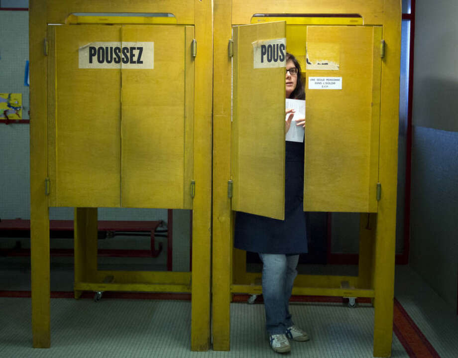 A Swiss voter leaves a polling box at a makeshift polling station after Swiss voters went to the polls to decide on a proposal to cap immigration to the Alpine republic, in the center of Geneva, Switzerland, Sunday, Feb. 9, 2014. The nationalist Swiss People's Party demands a stop for immigration to Switzerland. (AP Photo/Anja Niedringhaus)