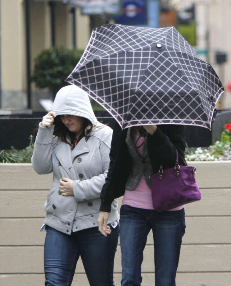 Umbrella and jacket hoods are called for as showers swept through Sacramento, Calif., Friday, Feb. 7, 2014. Drought-stricken California is getting some relief as a storm system the likes of which, forecasters say, the region has not seen in more than a year.(AP Photo/Rich Pedroncelli)