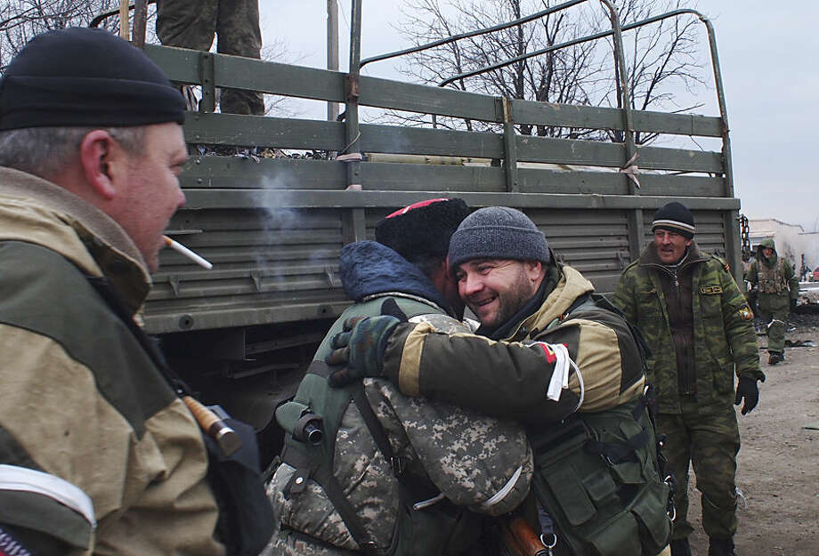 A pro-Russian rebel cossack, second left, hugs another rebel in Debaltseve, eastern Ukraine, Thursday, Feb. 19, 2015. After weeks of relentless fighting, the embattled Ukrainian rail hub of Debaltseve fell Wednesday to Russia-backed separatists, who hoisted a flag in triumph over the town. The Ukrainian president confirmed that he had ordered troops to pull out and the rebels reported taking hundreds of soldiers captive. (AP Photo/ Peter Leonard)