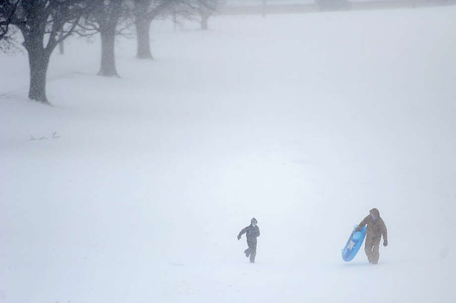Kyler Fairchild, left, and his father, John, run through blowing winds and snow after sledding down a hill at Helfrich Hills Golf Course, Wednesday, Feb. 18, 2015, in Evanville, Ind. The Indiana Department of Homeland Security is advising residents to prepare for temperatures near or below zero as a cold front moves in Wednesday. (AP Photo/The Evansville Courier & Press, Erin McCracken)