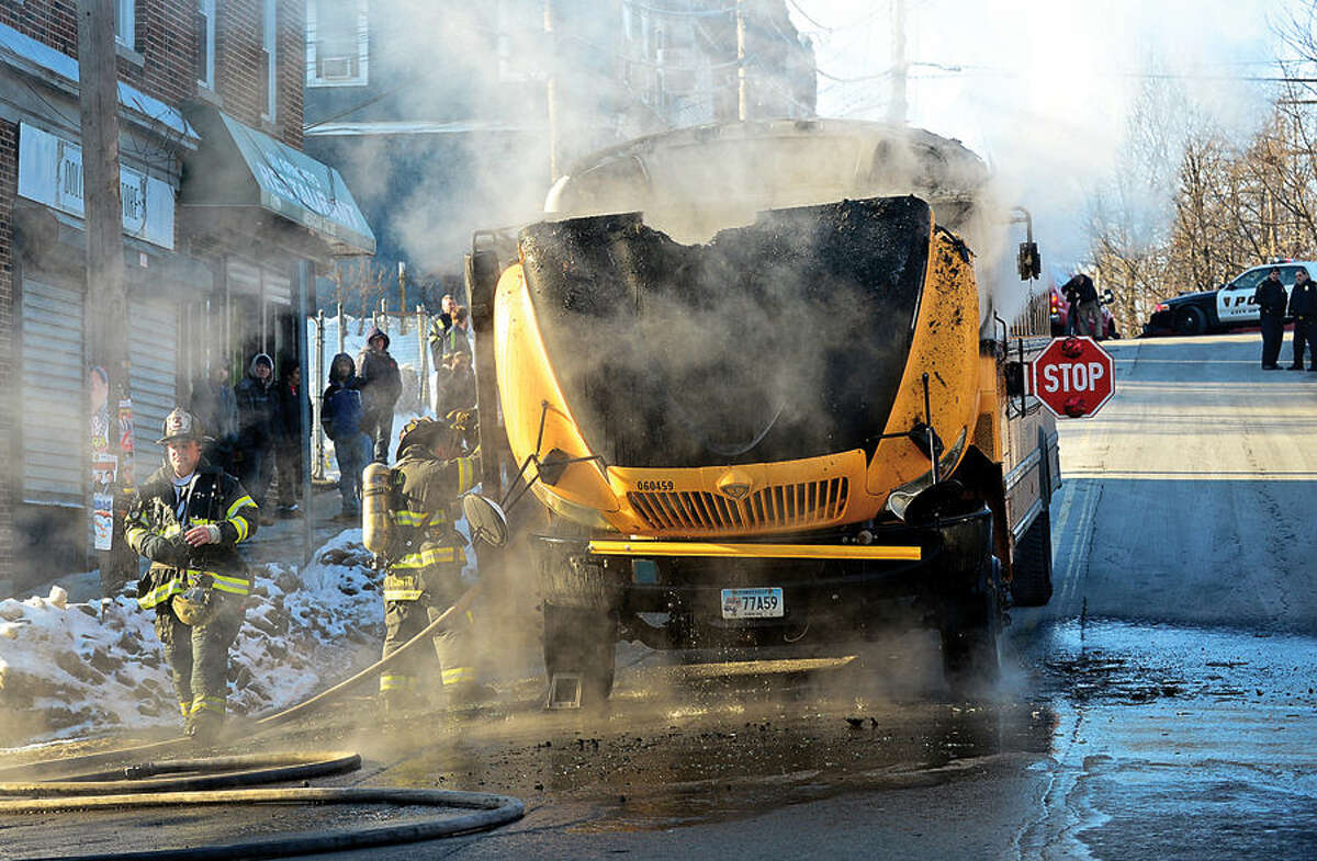 Hour photo / Erik Trautmann Norwalk firefihgters respond to a school bus fire at the corner of Lexiton and Ely Avenues Thursday morning. All students and the bus driver evacuated safely.