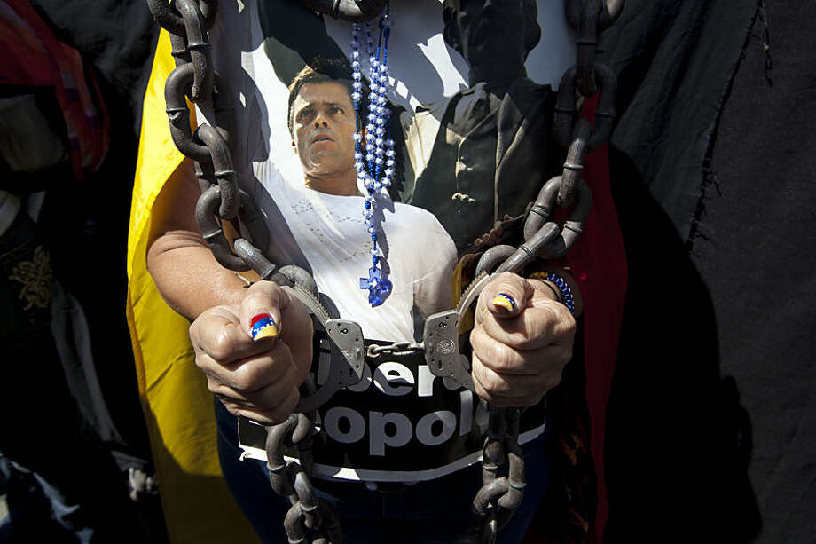 A woman wearing handcuffs, chains and a rosary holds a poster of jailed opposition leader Leopoldo Lopez at an event marking the one year anniversary of his arrest and imprisonment in Caracas, Venezuela, Wednesday, Feb. 18, 2015. One year has passed since Venezuela's streets were rocked by anti-government protests that left 43 people dead and neighborhoods disrupted by flaming barricades. The unrest culminated with the arrest of Lopez, a former Caracas-area mayor and key opposition leader. (AP Photo/Ariana Cubillos)