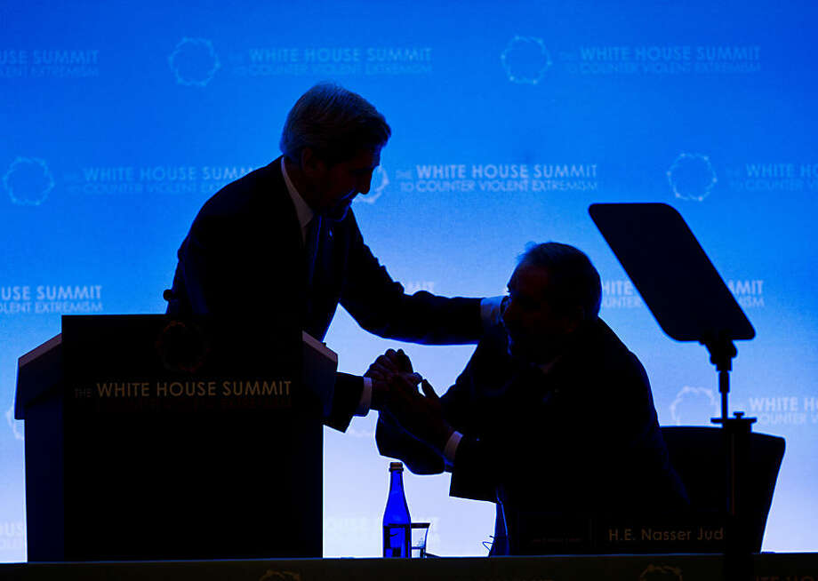 Secretary of State John Kerry, left, greets Jordan's Foreign Affairs Minister Nasser Judeh, right, as they are silhouetted on stage at the opening of the Countering Violent Extremism (CVE) Summit, Thursday, Feb. 19, 2015, at the State Department in Washington. The White House is conveying a three-day summit to bring together local, federal, and international leaders to discuss steps the US and its partners can take to develop community-oriented approaches to counter extremist ideologies that radicalize, recruit and incite to violence. (AP Photo/Pablo Martinez Monsivais)