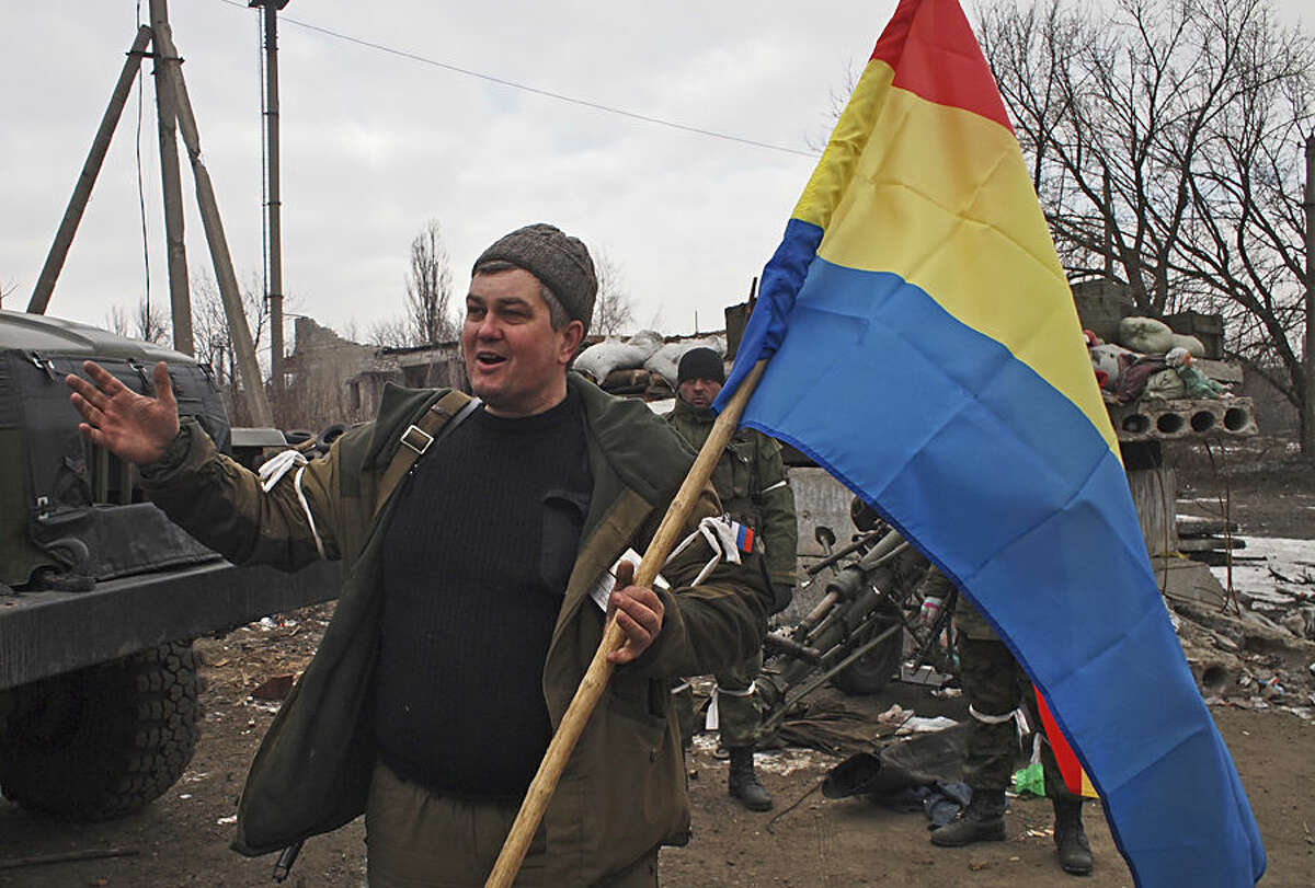 A pro-Russia rebel holds a flag of the rebel-held city of Luhansk in Debaltseve, eastern Ukraine, Thursday, Feb. 19, 2015. After weeks of relentless fighting, the embattled Ukrainian rail hub of Debaltseve fell Wednesday to Russia-backed separatists, who hoisted a flag in triumph over the town. The Ukrainian president confirmed that he had ordered troops to pull out and the rebels reported taking hundreds of soldiers captive. (AP Photo/ Peter Leonard)