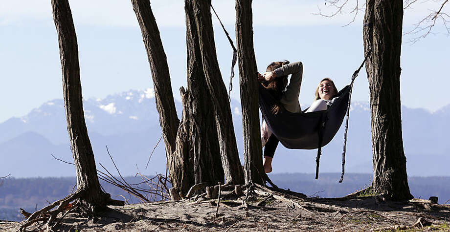 Taylor Wilkinson, right, and Karissa Courtney, both Seattle Pacific University students with the afternoon off, share a hammock overlooking the Puget Sound and the Olympic Mountains beyond Tuesday, Feb. 17, 2015, in Seattle. Temperatures hit record highs a day earlier, including 59 at Sea-Tac Airport, in parts of Washington and Oregon as one of the mildest winters continues in the Northwest. Forecasters expect more near-record temperatures on Tuesday because of a summer-like high pressure ridge that creates sunny, dry days. (AP Photo/Elaine Thompson)