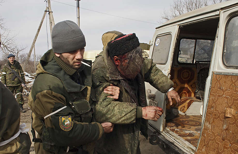 A wounded Cossack is carried away by fellow fighters after his car hit a land mine in the east Ukraine town of Debaltseve on Thursday, Feb. 19, 2015. After weeks of relentless fighting, the embattled Ukrainian rail hub of Debaltseve fell Wednesday to Russia-backed separatists, who hoisted a flag in triumph over the town. The Ukrainian president confirmed that he had ordered troops to pull out and the rebels reported taking hundreds of soldiers captive. (AP Photo/ Peter Leonard)