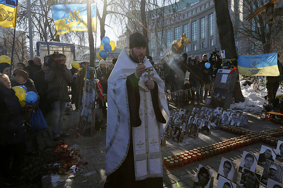 An Orthodox priest leads a service at a memorial dedicated to people who died in clashes with security forces in Kiev, Wednesday, Feb. 18, 2015. Municipal workers are preparing the square to commemorate the Maidan protest movement and the events which took place in late Feb. 2014 that led to the departure of former Ukrainian President Victor Yanukovich and the formation of a new government. (AP Photo/Sergei Chuzavkov)