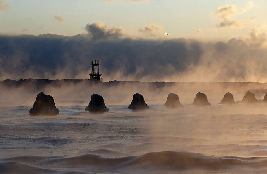 The sun rises above Lake Michigan as ice forms along the shore, Thursday, Feb. 19, 2015, in Chicago. Temperatures have dipped to as low as -13 in parts of Illinois with wind chills forecast to fall to between 20 and 30 degrees below zero. (AP Photo/Kiichiro Sato)