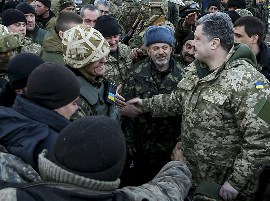 "Ukrainian President Petro Poroshenko, right, shakes hands with Ukrainian servicemen in the town of Artemivsk, Ukraine, Wednesday, Feb. 18, 2015. Poroshenko traveled to eastern Ukraine to ""shake the hands"" of the soldiers leaving Debaltseve. The Ukrainian president confirmed that he had ordered troops to pull out and the rebels reported taking hundreds of soldiers captive. (AP Photo/Mikhail Palinchak, Pool)"