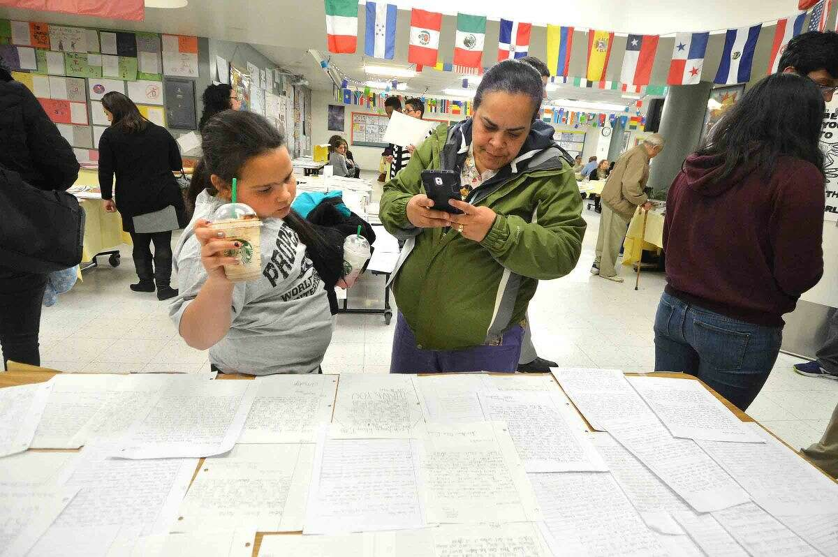 Hour Photo/Alex von Kleydorff Rebecca Colon-Evans and daughter Jace look at some of the hand written letters from Side by Side school at the 12th annual Courage to Speak Empowering Youth to be Drug Free family Night at West Rocks School