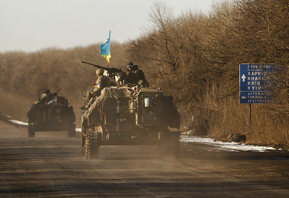 Ukrainian troops ride on an armored vehicle outside Artemivsk, Ukraine, while pulling out of Debaltseve, Wednesday, Feb. 18, 2015. After weeks of relentless fighting, the embattled Ukrainian rail hub of Debaltseve fell Wednesday to Russia-backed separatists, who hoisted a flag in triumph over the town. The Ukrainian president confirmed that he had ordered troops to pull out and the rebels reported taking hundreds of soldiers captive. (AP Photo/Vadim Ghirda)