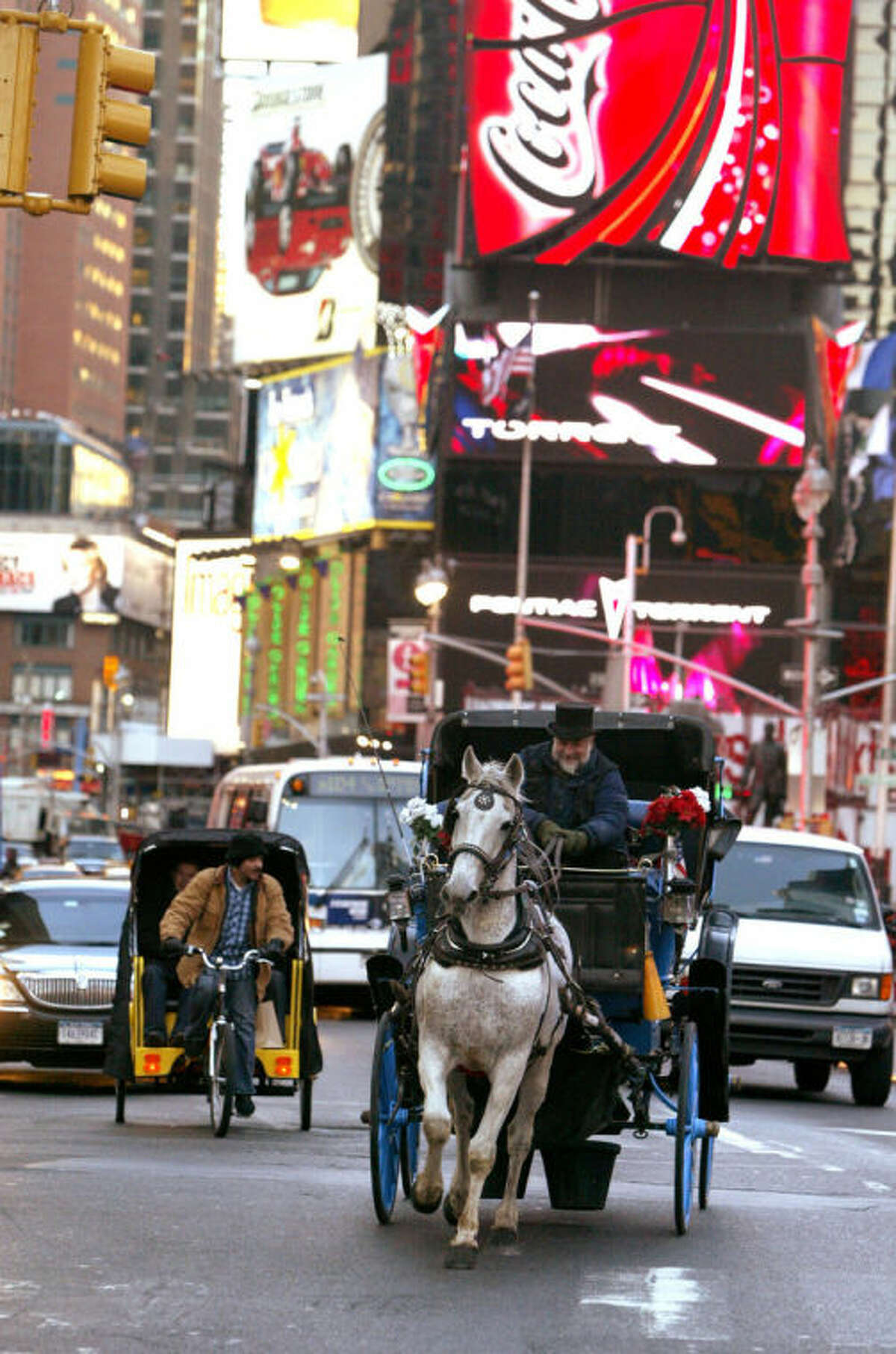 FILE- In this March 1, 2006, file photo, a pedicab driver, left, and a horse-drawn carriage make their way down Broadway in New York's Times Square. New York City Mayor Bill de Blasio seeks to shut down the city?'s horse-drawn-carriage industry, believing that it was less than humane to put horses on busy New York City streets. Carriage-horse drivers counter that their industry provides homes for surplus horses from farms and the racing industry that would otherwise be shipped off to slaughterhouses. (AP Photo/Mary Altaffer, File)