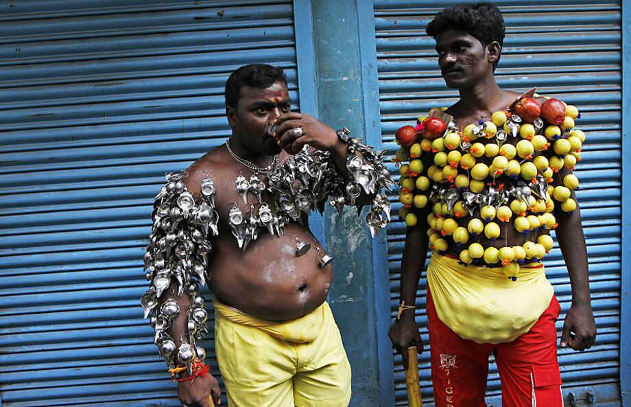 Hindu devotees, their bodies pierced with lemon and paladai, or bowl with a spout mainly used to feed milk to infants, wait to participate in a procession to mark Shivratri, or the night of Shiva, in Chennai, India, Wednesday, Feb. 18, 2015. Such processions are held as an offering and show of devotion by devotees on the day dedicated to the worship of Lord Shiva, the Hindu god of destruction. (AP Photo/Arun Sankar K)