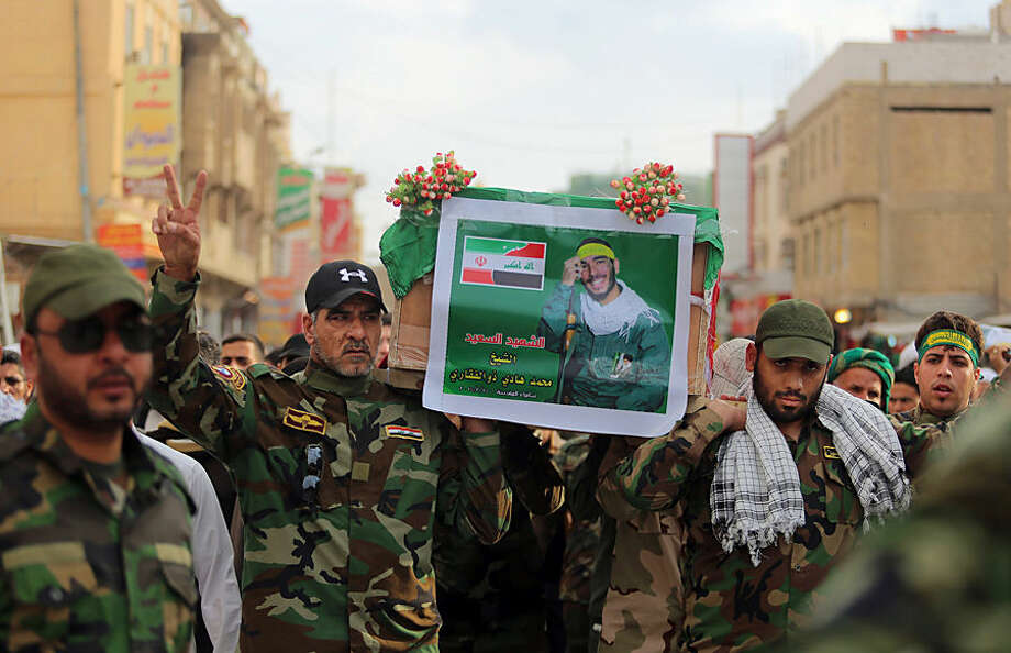 Iraqi and Iranian Shiite militiamen carry the coffin draped with Iranian flag during a funeral procession for Mohammad Hadi Zulfiqar, in the poster, an Iranian volunteer fighting in the Badr Brigades Shiite militia, in Najaf, 100 miles (160 kilometers) south of Baghdad, Iraq, Thursday, Feb. 19, 2015. Zulfiqar was killed during a battle against the Islamic State extremist group in Samarra, a town north of Baghdad that is home to a major Shiite shrine. (AP Photo/Jaber al-Helo)