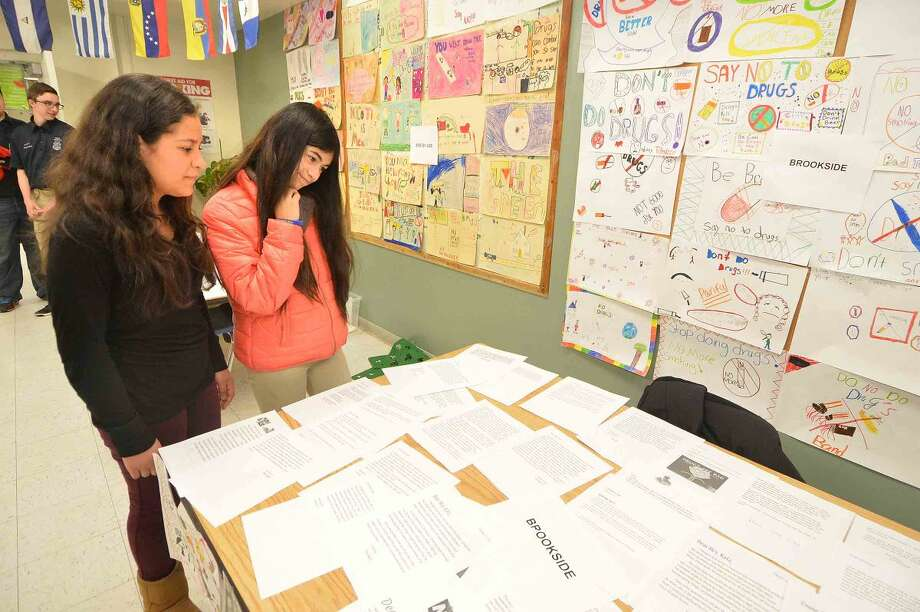 Hour Photo/Alex von Kleydorff Roton School 7th graders Abigail Garcia and Andrea Mandujano look over some of the hundreds of students letters at the 12th annual Courage to Speak Empowering Youth to be Drug Free family Night at West Rocks School