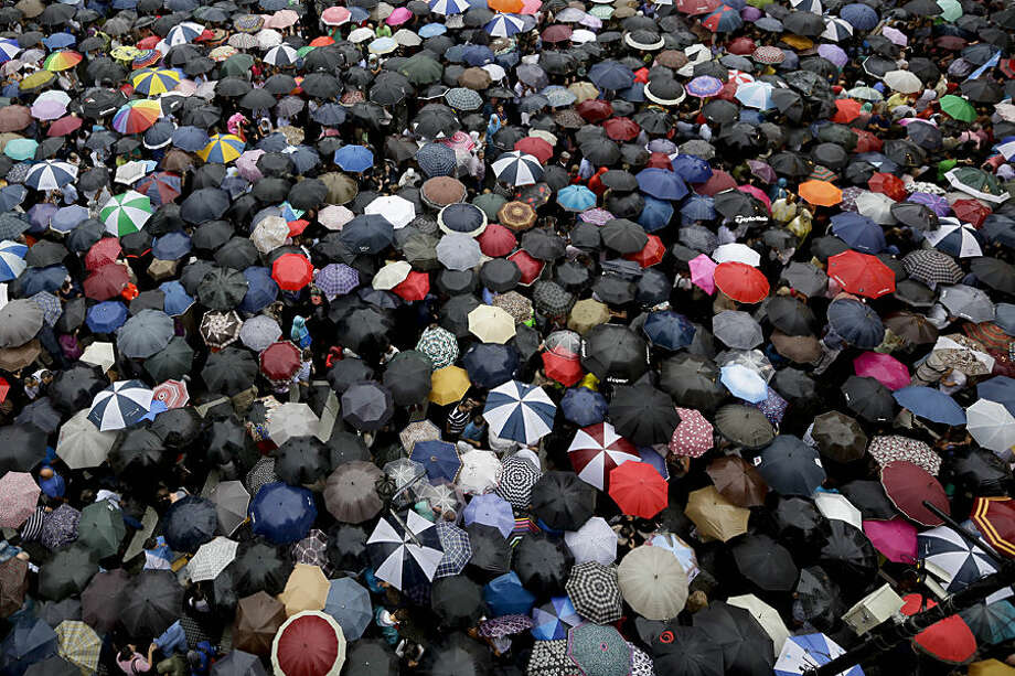 People holding umbrellas gather in Plaza de Mayo to demand answers from the government in the mysterious death of prosecutor Alberto Nisman one month ago in Buenos Aires, Argentina, Wednesday, Feb. 18, 2015. Nisman was found dead of a gunshot wound Jan. 18, hours before he was to detail to Congress his explosive accusations that President Cristina Fernandez and top administration officials orchestrated a secret deal with Iran to shield officials allegedly responsible for the 1994 bombing of a Jewish community center in Buenos Aires. (AP Photo/Victor R. Caivano)