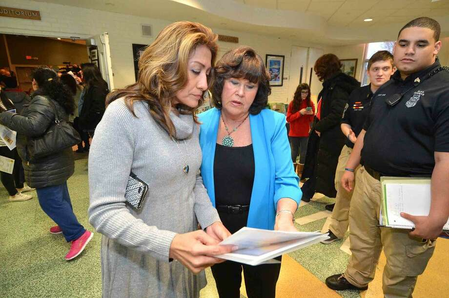 Hour Photo/Alex von Kleydorff Lucia Rilling and Ginger Katz look over the program for the 12th annual Courage to Speak Empowering Youth to be Drug Free family Night at West Rocks School