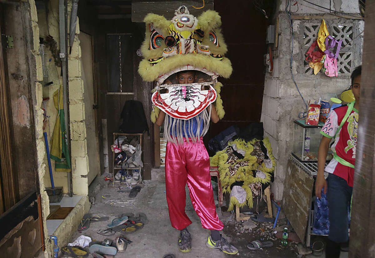 In this Wednesday, Feb. 18, 2015 photo, a Filipino lion dancer checks his costume as he prepares for a performance in Manila's Chinatown, Philippines. The Pink Panther Dragon and Lion Dance Group, a business operated by eight Filipino siblings who live in a creekside slum in Manila's Chinatown area, are hired by businesses that believe a Chinese New Year peformance will drive misfortunes away and bring good luck. (AP Photo/Aaron Favila)