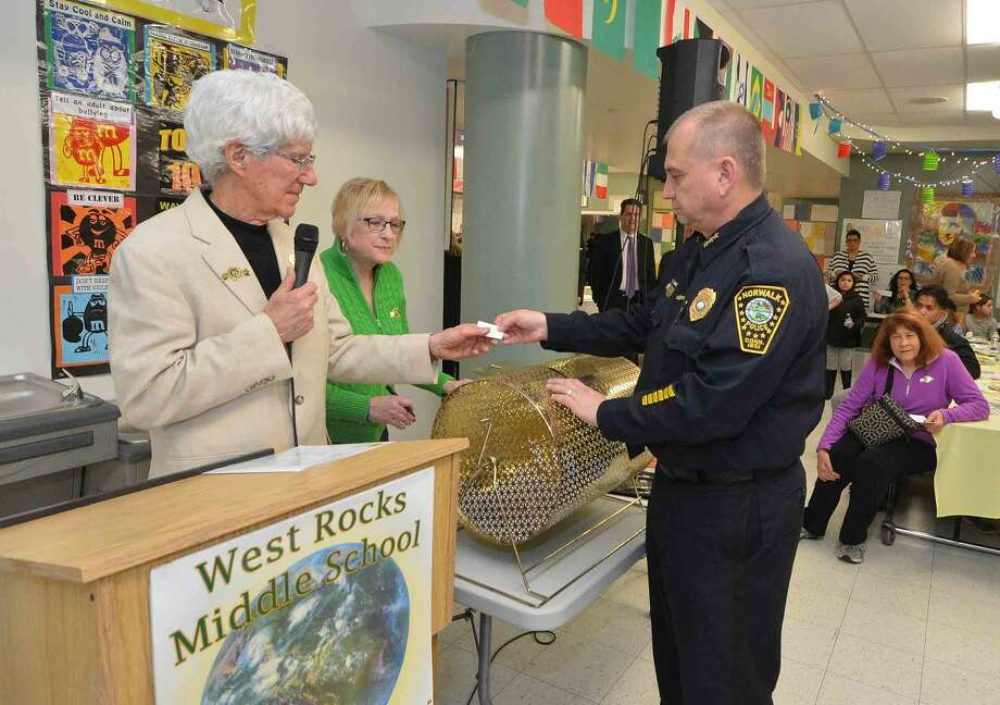 Hour Photo/Alex von Kleydorff Norwalk Police Chief Tom Kulhawik pulls some winning raffle tickets during the 12th annual Courage to Speak Empowering Youth to be Drug Free family Night at West Rocks School