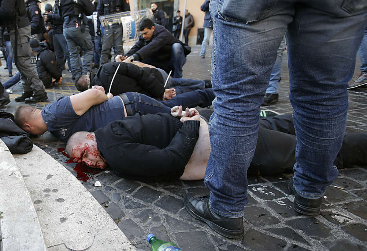 An injured Feyenoord's fan lies on the ground after being arrested with others during clashes occurred with Italian Policemen at the Spanish steps prior to the start of the Europa League soccer match between Roma and Feyenoord in Rome, Thursday, Feb. 19, 2015. (AP Photo/Gregorio Borgia)