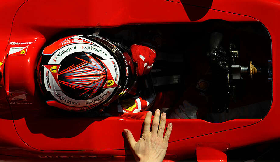 Kimi Raikkonen of Finland and Ferrari is pulled by technicians to the garage during the 2015 Formula One testing at the Barcelona Catalunya racetrack in Montmelo, Spain, Thursday, Feb. 19, 2015. (AP Photo/Manu Fernandez)