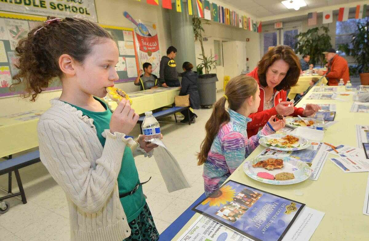Hour Photo/Alex von Kleydorff Brookside School 4th grader Talia Hull enjoys a cookie after dinner with her family at the 12th annual Courage to Speak Empowering Youth to be Drug Free family Night at West Rocks School