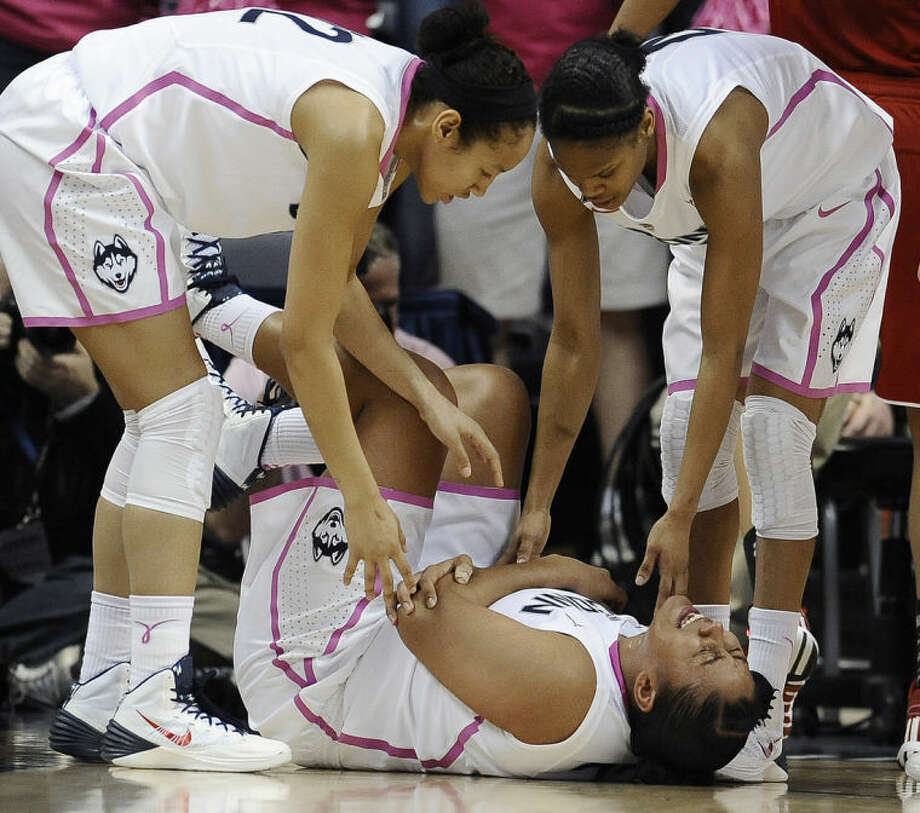 Connecticut's Kaleena Mosqueda-Lewis holds her arm after a hard fall to the court as teammates Saniya Chong, left, and Moriah Jefferson, right, look over her during the first half of an NCAA college basketball game on Sunday, Feb. 9, 2014, in Storrs, Conn. (AP Photo/Jessica Hill)