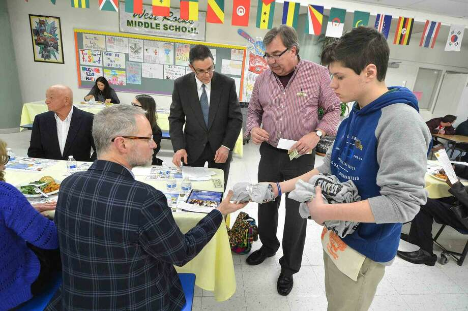 Hour Photo/Alex von Kleydorff Ric Meyer buys some raffle tickets and gets a free T-Shirt from Greg Gilbertson and Joe Boccuzzi at the 12th annual Courage to Speak Empowering Youth to be Drug Free family Night at West Rocks School