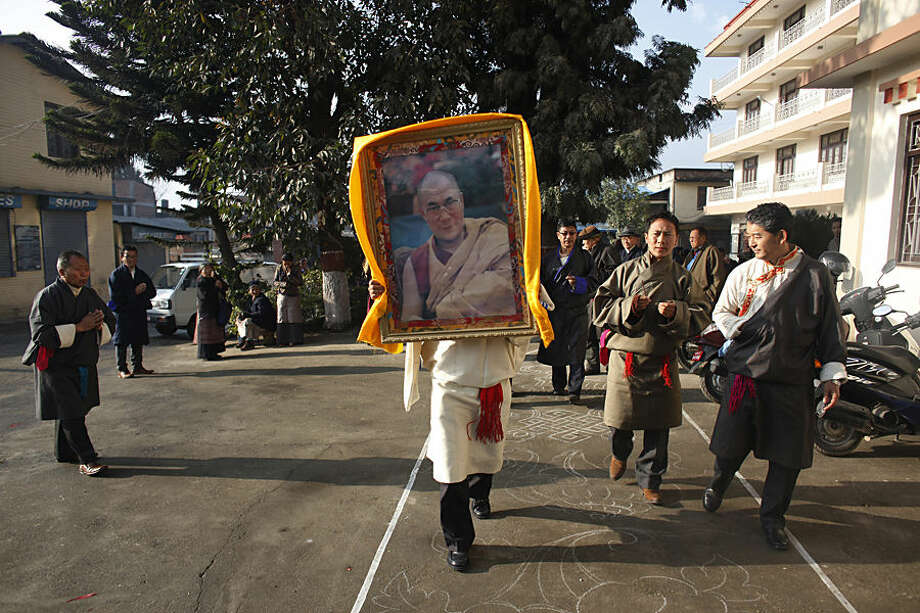 A Tibetan man carries a portrait of spiritual leader the Dalai Lama during Tibetan New Year, or Losar, inside the Tibetan Refugee Camp in Lalitpur, Nepal, Thursday, Feb. 19, 2015. Tibetans across the world marked the arrival of the New Year with prayers and festivities. (AP Photo/Niranjan Shrestha)