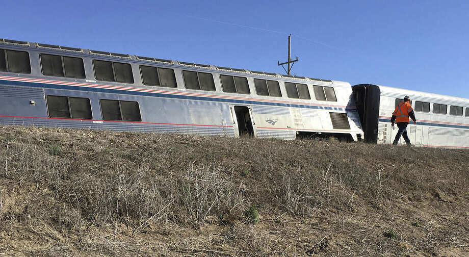 A railroad worker walks past one of the Amtrak cars that derailed west of Dodge City, Kansas early Monday, March 14, 2016, injuring multiple people who were transferred to hospitals in Garden City and Dodge City, according to a release from Amtrak. The Amtrak train carrying 131 passengers derailed in rural Kansas moments after an engineer noticed a significant bend in a rail and applied the emergency brakes, an official said. (Oliver Morrison /The Wichita Eagle via AP) LOCAL TELEVISION OUT; MAGS OUT; LOCAL RADIO OUT; LOCAL INTERNET OUT; MANDATORY CREDIT