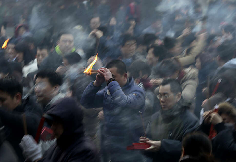 A man holds burning incense as he offers prayers on the first day of the Chinese Lunar New Year at Yonghegong Lama Temple in Beijing, China Thursday, Feb. 19, 2015. Chinese people are celebrating the arrival of the Lunar New Year, the Year of the Sheep. (AP Photo/Andy Wong)
