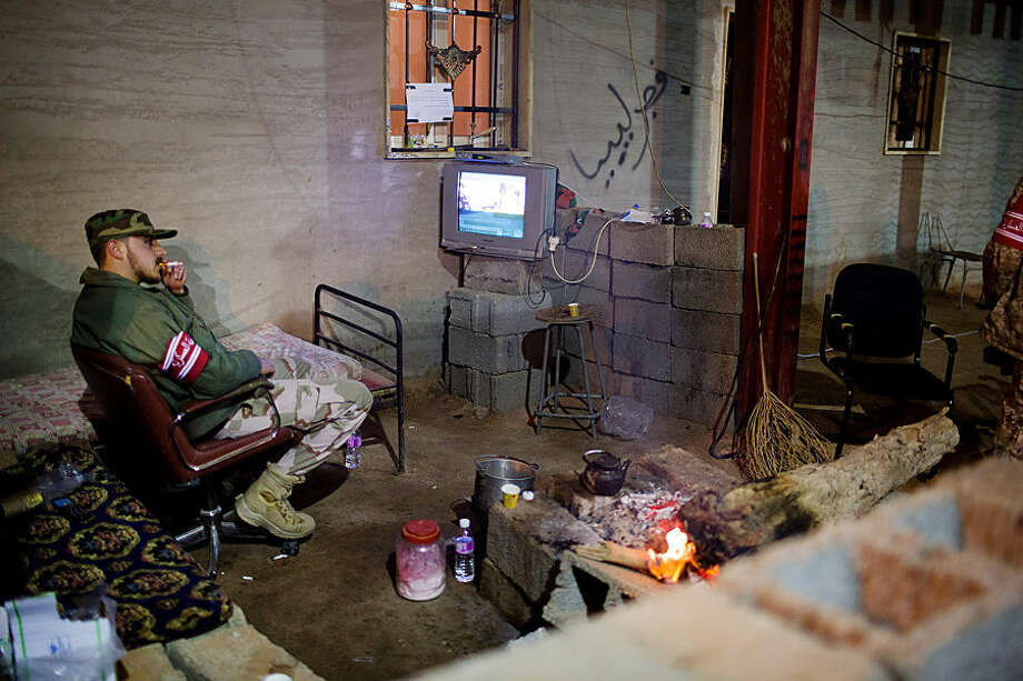 In this Wednesday, Feb. 18, 2015 photo, a Libyan military soldier smokes his cigarette as he watches the news during his break, 110 kilometers (68 miles) from Sirte, Libya. (AP Photo/Mohamed Ben Khalifa)