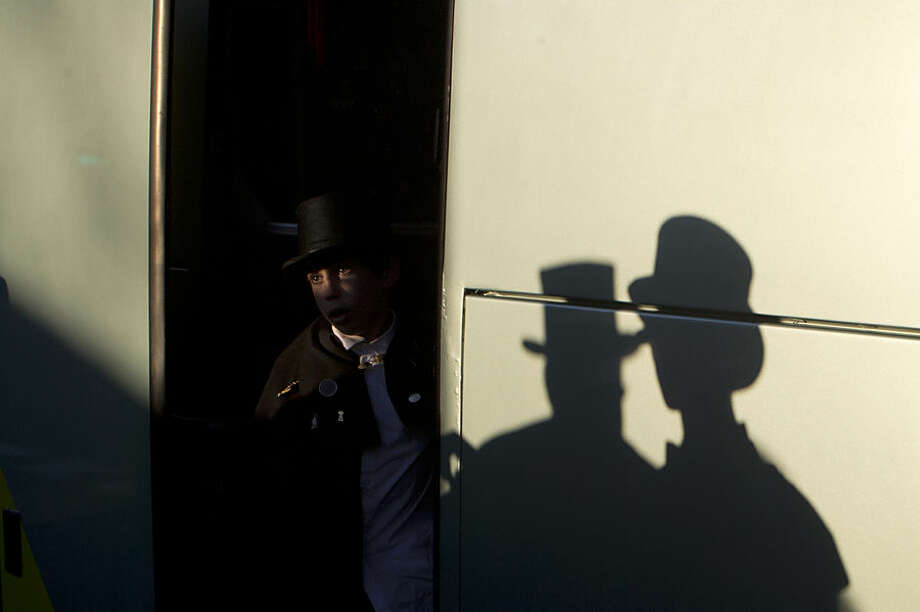 A member of the Alegre brotherhood steps off a bus upon his arrival for a mock funeral procession in Madrid, Spain, Wednesday, Feb. 18, 2015. The funeral procession traditionally marks the end the carnival. (AP Photo/Paul White)