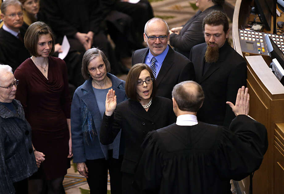 Oregon Secretary of State Kate Brown is sworn in as Oregon Governor by Oregon Chief Justice Thomas A. Balmer in Salem, Ore., Wednesday, Feb. 18, 2015. John Kitzhaber, elected to an unprecedented fourth term last year, announced last week that he would step down amid allegations his fiancee used her relationship with him to enrich herself. (AP Photo/Don Ryan)